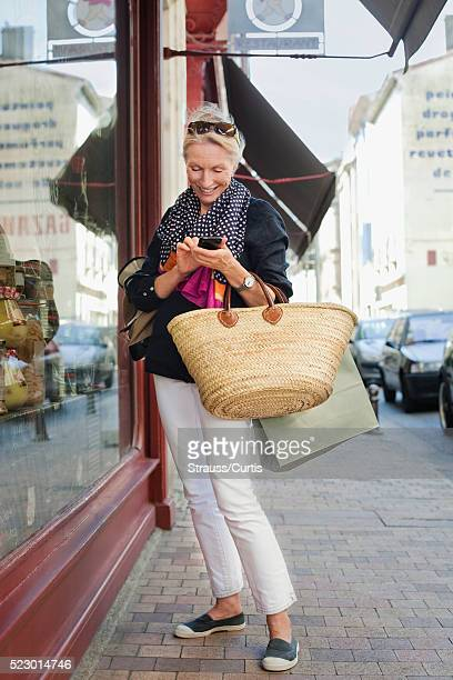 Woman texting while window shopping, Carcassonne, France