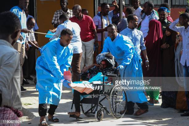 TOPSHOT A woman that was wounded during the bombing attack is pushed on a wheel chair at the Madina Hospital in Mogadishu on December 28 2019 A...