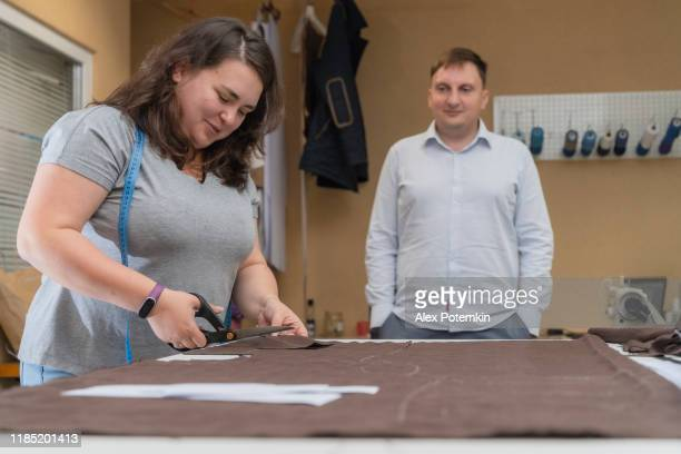woman, the tailor, working in the small sewing atelier when a man, client, waiting in the backdrop. - alex potemkin or krakozawr stock pictures, royalty-free photos & images
