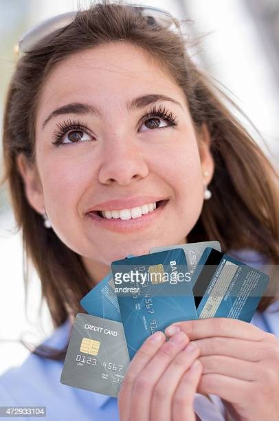 Woman thinking and holding credit cards