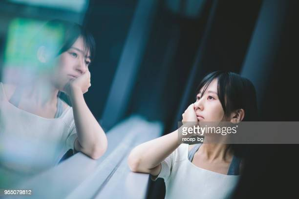 woman thinking deeply by the window - mulher japonesa imagens e fotografias de stock