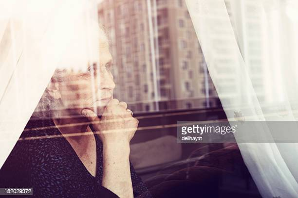 A woman thinking deeply whilst looking out of a window