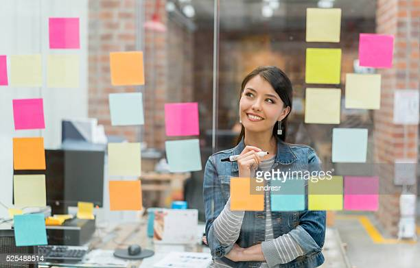 woman thinking of ideas at the office - voorbereiding stockfoto's en -beelden