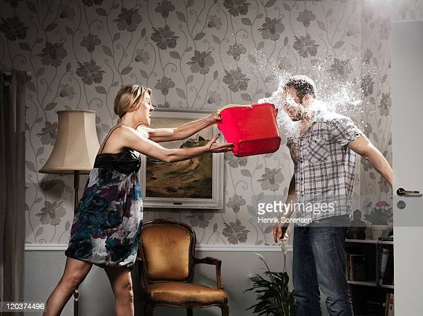 woman thowing a bucket of water at her partner - couple arguing stock photos and pictures