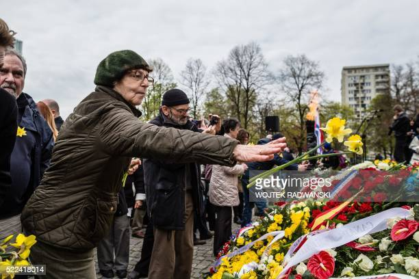 A woman thows flowers at the Warsaw Ghetto Uprising monument during festivities to mark the Warsaw Ghetto uprising's 73th anniversary on April 19...