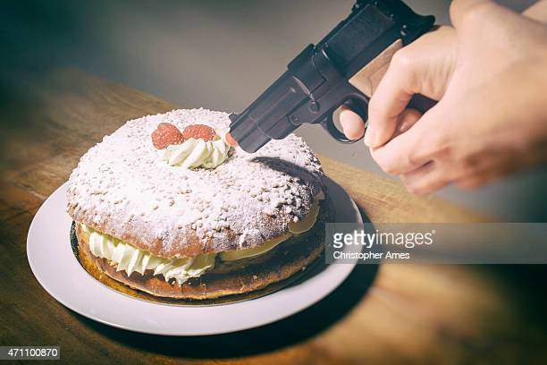 woman threatens delicious cream cake with toy hand gun - prejudice stock photos and pictures