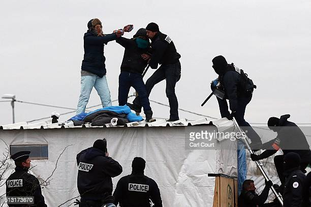 A woman threatens to cut her wrist with a knife as French police remove her and a man from the top of a hut as they clear the jungle migrant camp on...
