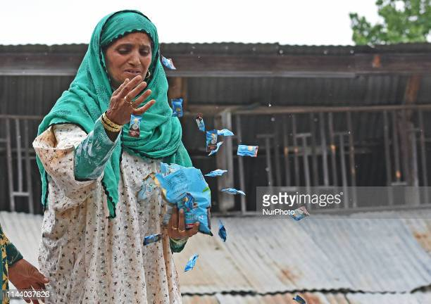 A woman throw candies upon seeing the body of top militant commander Naseer Pandith in his native village Kareemabad in south Kashmir's Pulwama on...