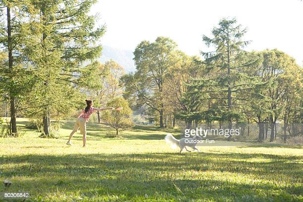 Woman throwing a frisbee, with dog