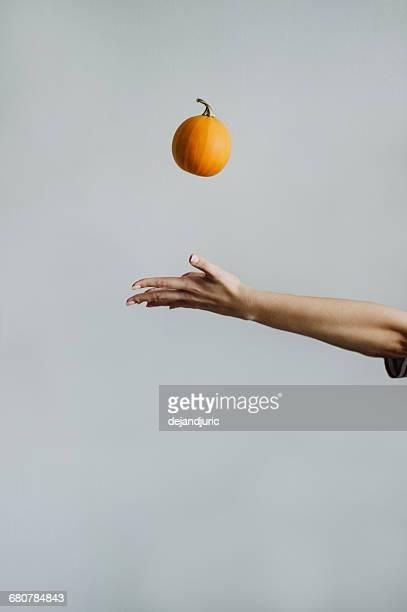 Woman throwing a miniature pumpkin in the air