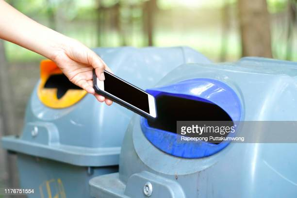 woman throwing a phone into the trash - throwing stock pictures, royalty-free photos & images