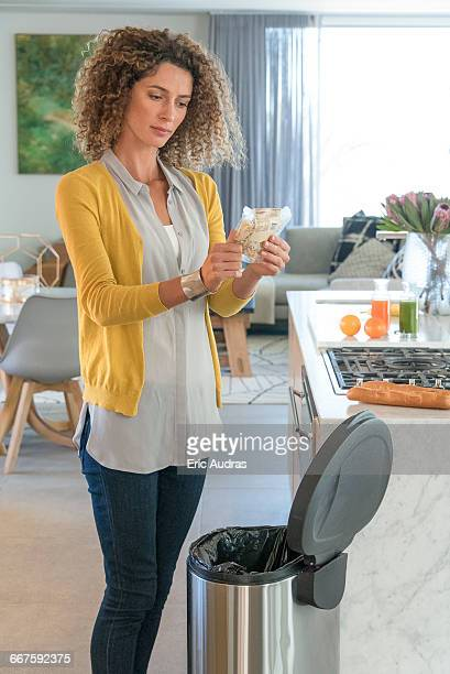 Woman throwing a sachet of food in garbage bin
