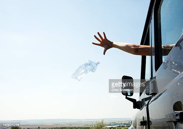 woman throwing bottle out car window - lanciare foto e immagini stock