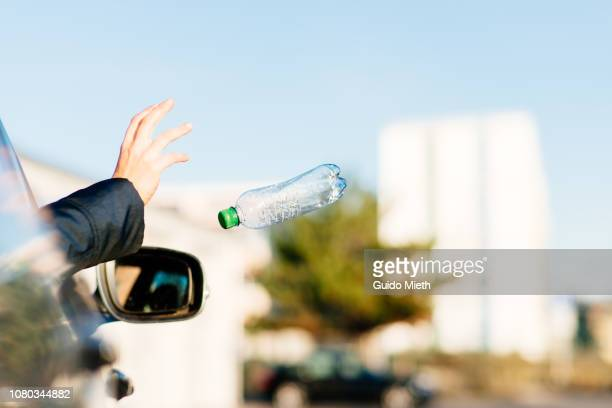 woman throwing bottle out of car window. - lanciare foto e immagini stock