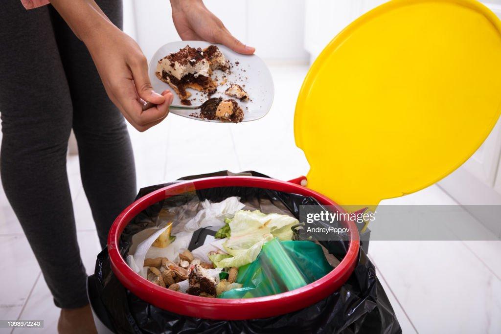 Woman Throwing Cake In Trash Bin : Stock Photo