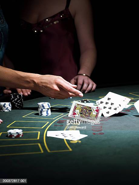 Woman throwing cards on gaming table, close-up