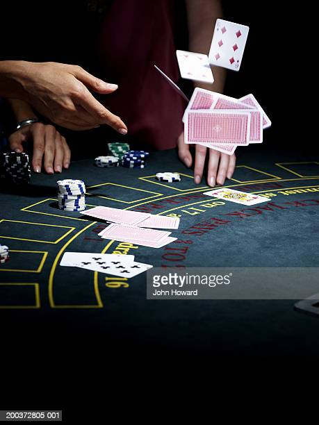 Woman throwing cards onto gaming table, close-up