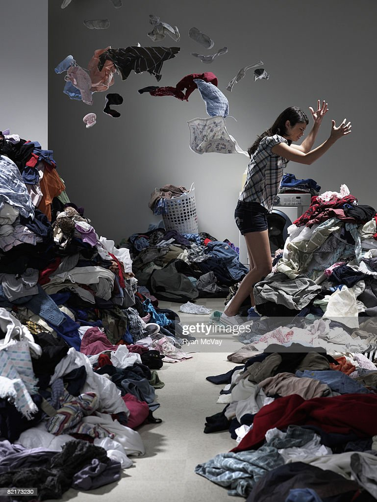 Woman throwing clothes in overflowing laundry room : Stock Photo