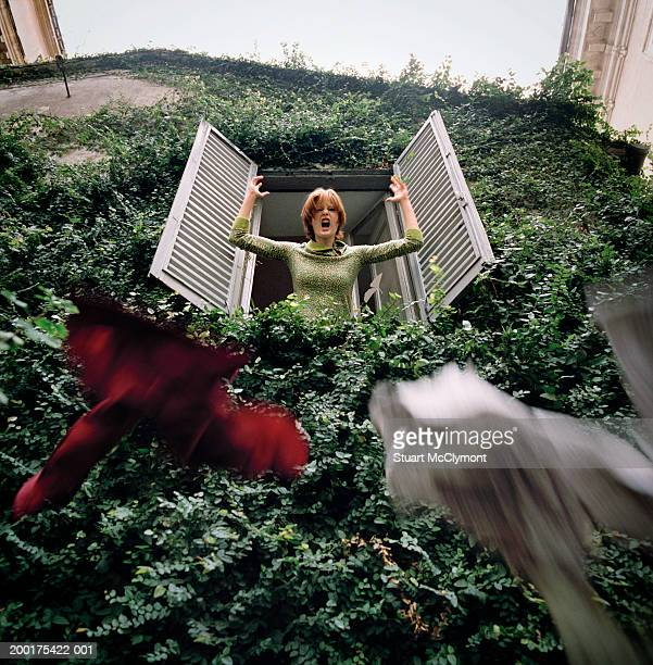 Woman throwing clothes out of window surrounded by ivy, low angle view