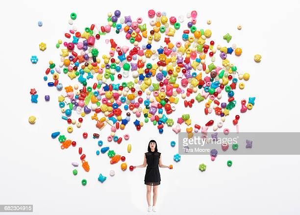 woman throwing colourful beads up