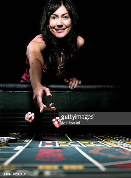 woman throwing dice on gaming table, smiling, portrait - gambling stock pictures, royalty-free photos & images