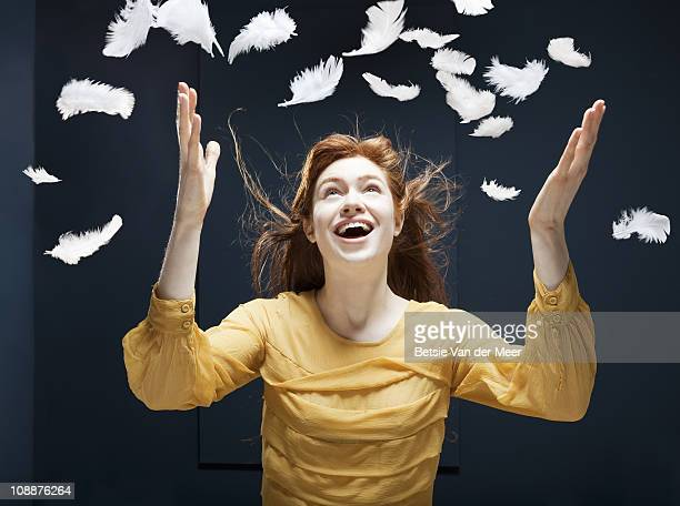 woman throwing feathers up in wind.