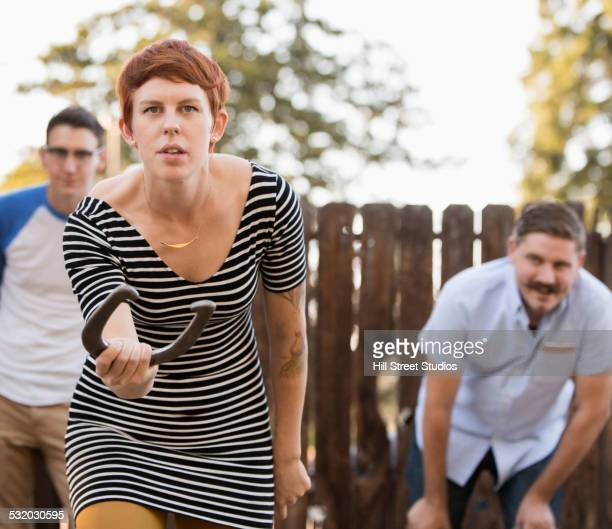 Woman throwing horseshoe in game outdoors