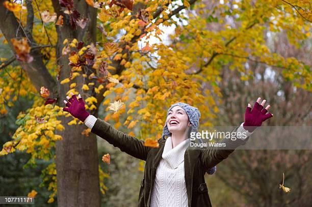 Woman throwing leaves in air.