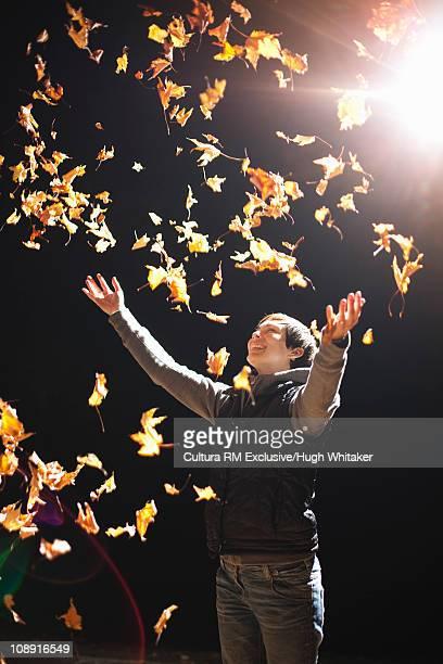 Woman throwing leaves in air