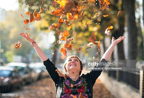 woman throwing leaves in autumn - jcbonassin stock pictures, royalty-free photos & images