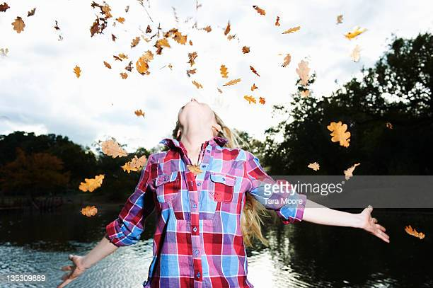 woman throwing leaves up in sky in park - falling stock pictures, royalty-free photos & images