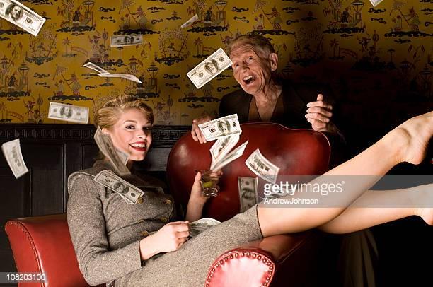 Frau werfen Geld, in der Luft mit älteren Mannes.