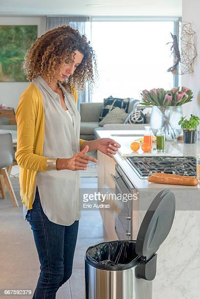 woman throwing sachet of food in garbage bin - garbage can stock photos and pictures