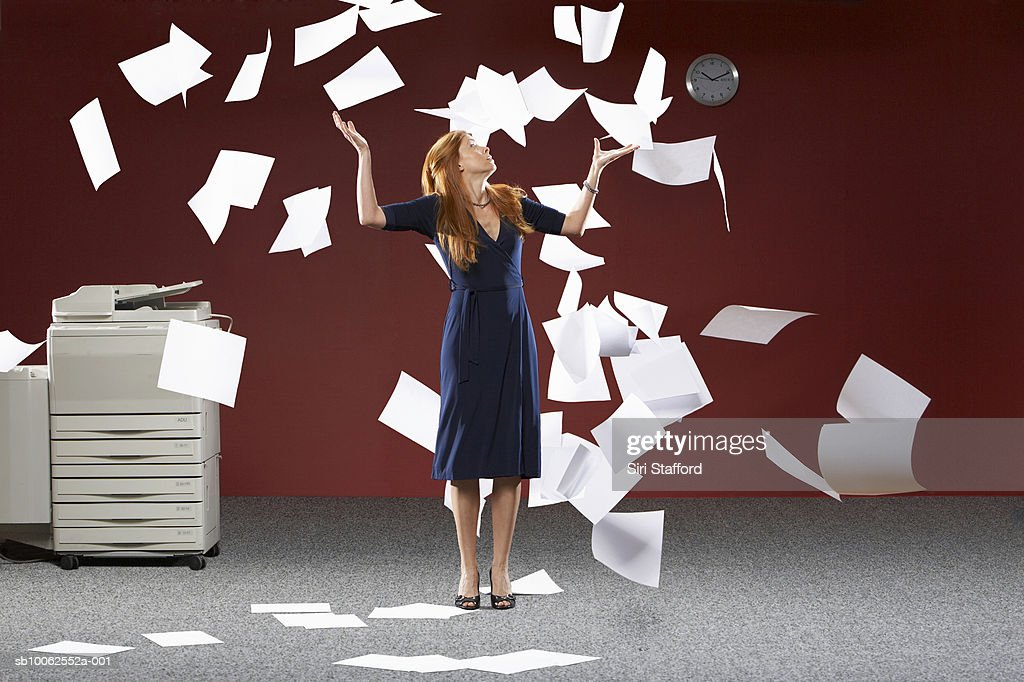 Woman throwing sheets of papers in air : Stock Photo