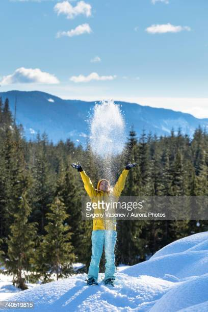 Woman throwing snow in air, Whistler, British Columbia, Canada