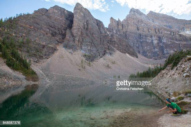 woman throwing stones into lake agnes, banff national park, canada - christina felschen stock pictures, royalty-free photos & images
