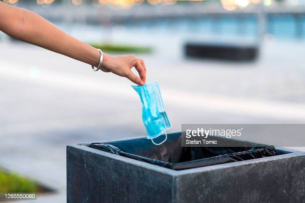 woman throwing used protective surgical mask into the garbage bin - arremessar imagens e fotografias de stock