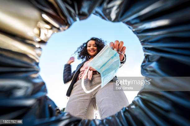 woman throwing used protective surgical mask into the garbage bin from inside - arremessar imagens e fotografias de stock