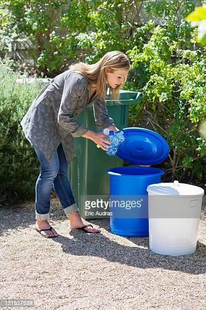 woman throwing water bottles in garbage bin - bending over stock pictures, royalty-free photos & images