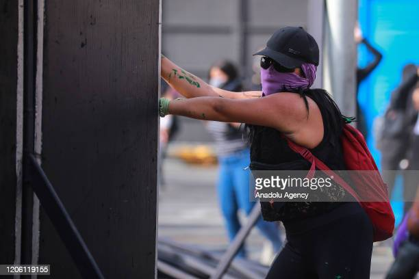 A woman throws a barrier during a protest on the International Women's Day in Mexico City Mexico on March 8 2020