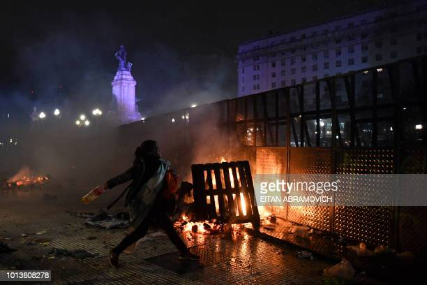TOPSHOT A woman throws a bottle to riot police agents outside the National Congress in Buenos Aires on August 9 after senators rejected the bill to...