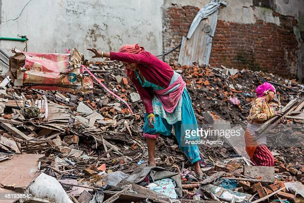 Woman throws a cardboard piece as she clears debris from a destroyed building in Kathmandu on July 25, 2015. Today marks the 3 month anniversary of...