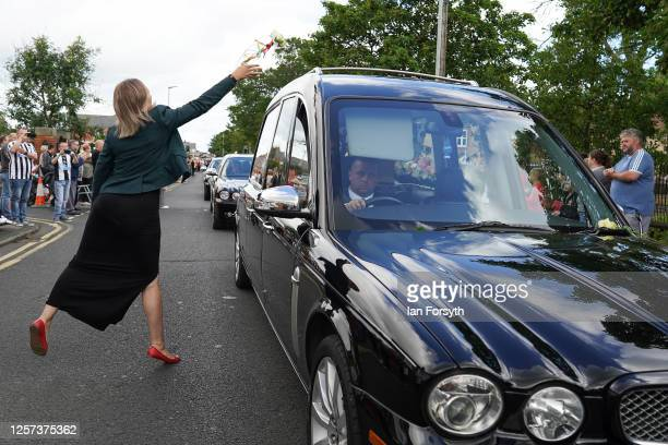 A woman throws a flower on the hearse as the funeral cortege for Jack Charlton passes through his childhood home town on July 21 2020 in Ashington...