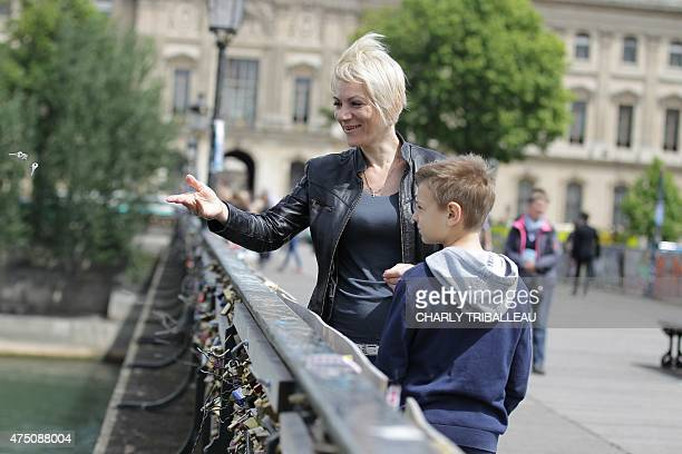 A woman throws a padlock's key in the Seine river after locking a padlock on the Pont des Arts on May 29 2015 in Paris as the Paris municipalty...