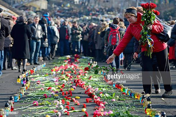 A woman throws a rose down onto a pathway of flowers placed in Independence Square for the antigovernment demonstrators who were killed in clashes...