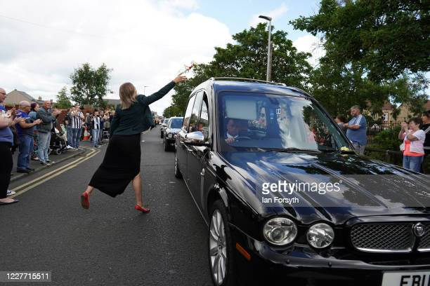A woman throws a tribute over the hearse as people line the streets to pay tribute to Jack Charlton as his funeral cortege passes through his...