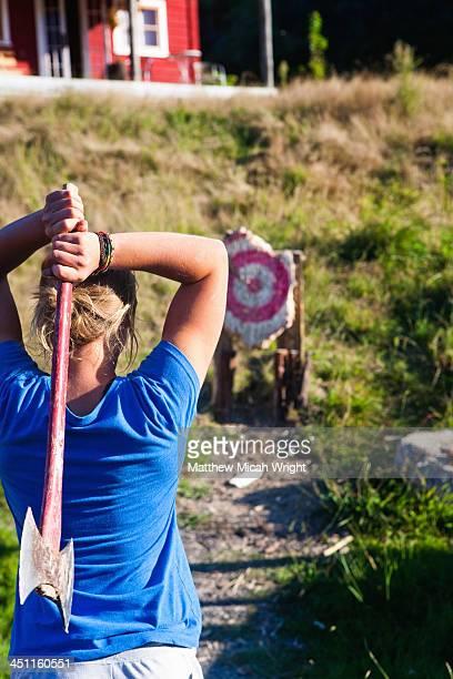 A woman throws an axe at a target.