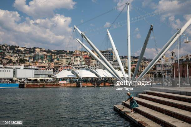 A woman throws food for the fish from steps in the Port of Genoa on August 19 2018 in Genoa Italy 43 people were killed after a large section of the...