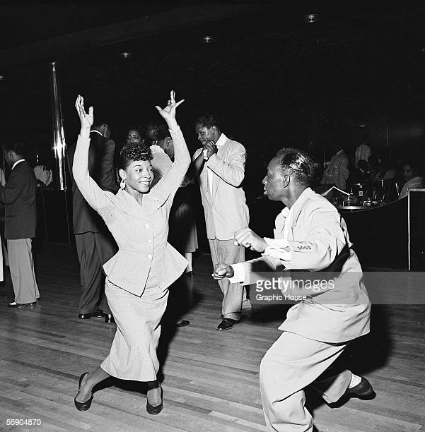 A woman throws her arms in the air like she just doesn't care as she swing dances with a man at the Savoy Ballroom Harlem New York late 1940s