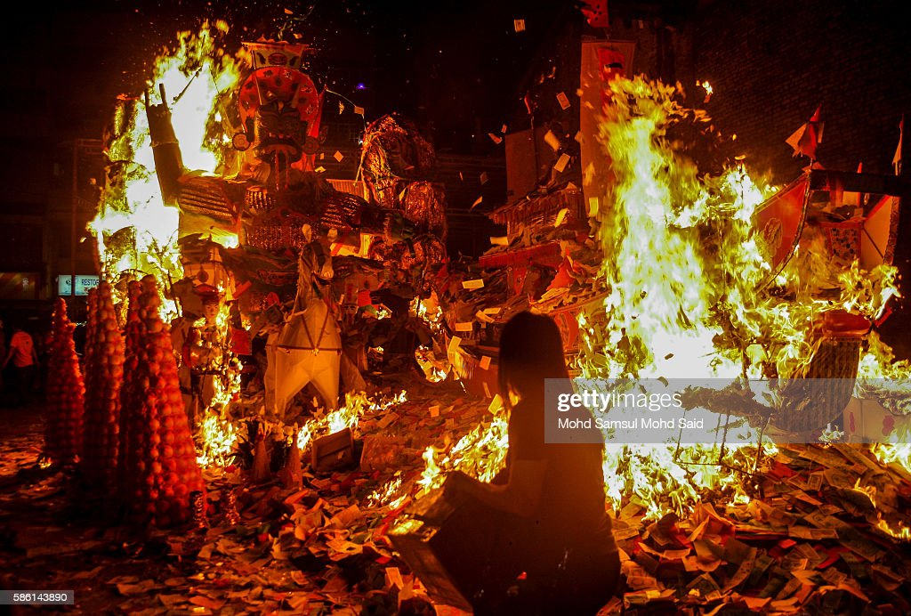 A woman throws prayer paper on to the fire during the Hungry Ghost Festival on August 6, 2016 in Kuala Lumpur, Malaysia. The Hungry Ghost Festival falls on the 15th day of the seventh lunar month. According to traditional Chinese belief, the seventh month in the lunar calendar is when restless spirits roam the earth. Many Chinese people make efforts to appease these transient ghosts, while feeding their own ancestors particularly on the 15th day, which is the Yu Lan or Hungry Ghost Festival.